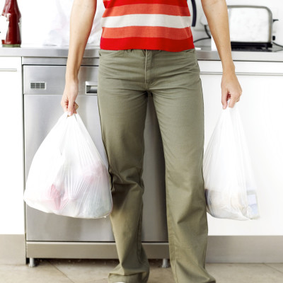 Woman Holding Plastic Bags with Groceries --- Image by © Royalty-Free/Corbis